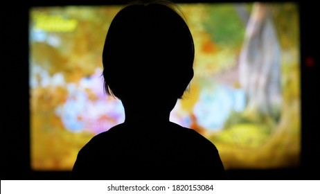Little child silhouette back looking at TV screen watch cartoons, abandoned