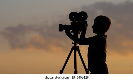 Petite silhouette d'enfant avec caméra professionnelle proche du coucher du soleil, un loisir précoce
