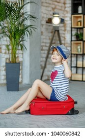 Little child sits on a red suitcase in a hat. Concept, lifestyle, childhood, trip, vacation, family, tourism.