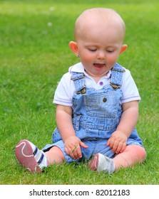 Little child sitting on a grass.