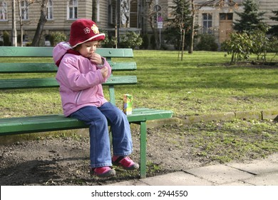 little child sitting on a green bench and drinking