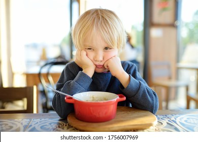 Little child sitting the table in cafe or restaurant and doesn't want to eat. Healthy food. Kids diet. Poor appetite. Grandmother upbringing.