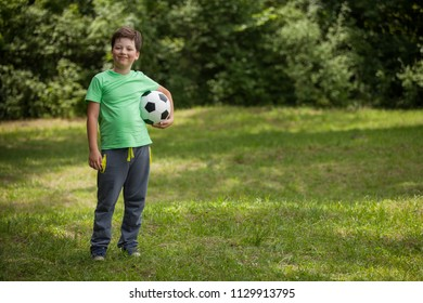Little child soccer player. Boy with ball on green grass.