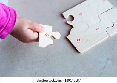 Little child solving a puzzle.