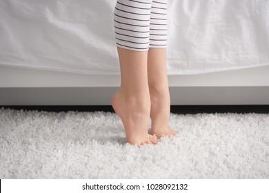 Little child standing near bed, closeup