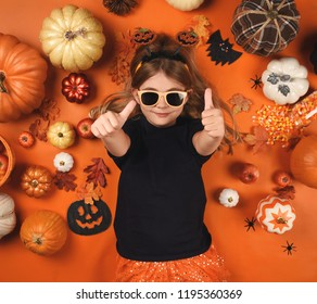 A little child is surrounded by Halloween decoration items such as leaves, candy corn and pumpkins on an orange background for a celebration concept.