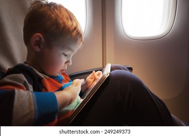 Little child with tablet computer on the lap sitting by the illuminator in the plane