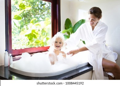 Little child taking bubble bath in beautiful bathroom with big garden view window. Mother washing baby. Kids hygiene. Shampoo, hair treatment and soap foam for children. Mom bathing kid in large tub.