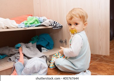 little child throws clothes from the closet at home