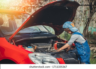 Little child trying to fix broken real car. Dreaming to be auto technician