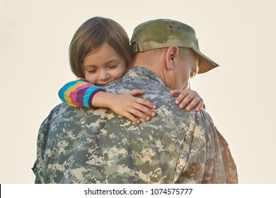 Little child is very happy her father came back from army. Little kid is hugging her father.