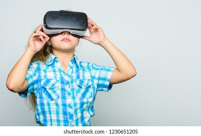 Little child in VR headset. Small child wear wireless VR glasses. Little girl wearing virtual reality goggles. Happy kid use modern technology. Digital future and innovation. Another reality is here.