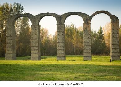 Little child walking under roman aqueduct in Acqui Terme