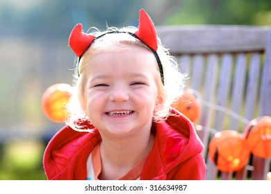 Little child wearing devil's hairband and red coat decorating garden with pumpkins garland.