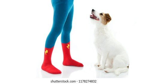 LITTLE CHILD WEARING HERO SOCK OR TIGHTS TRAINNING HIS DOG IN OBEDIENCE. ISOLATED AGAINST WHITE BACKGROUND.