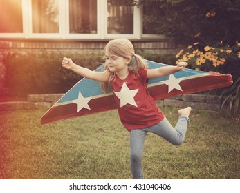 A little child is wearing homemade cardboard flying wings with stars on them pretending to be a pilot for a craft, imagination or exploration concept.