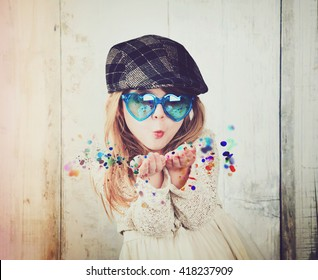 A little child is wearing sunglasses and blowing magical rainbow glitter sparkles in the air for a celebration, happiness or party idea.