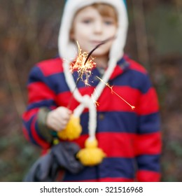 Little child in winter clothes holding burning sparkler on New Year's Eve. Safe fireworks for kids concept. Happy kid boy outdoors.