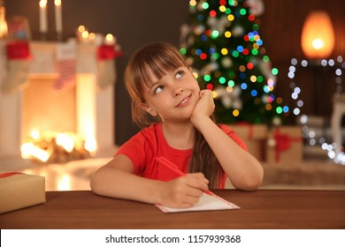 Little child writing letter to Santa at home. Christmas celebration
