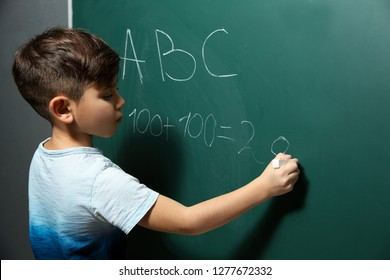 Little child writing letters and doing math on green blackboard
