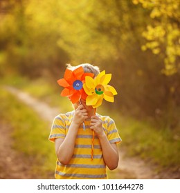 Little child with yellow and orange pinwheels on green forest background in sunny day