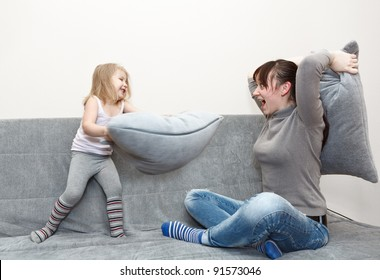 Little child and young mother pillow fighting on the sofa.