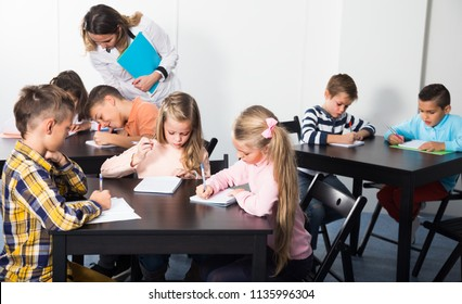 Little children with adult teacher in classroom