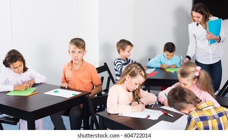 Little children with attentive teacher drawing in classroom on the lesson