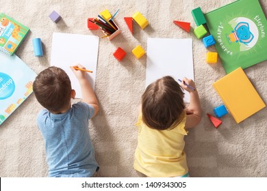 Little children drawing indoors, top view. Learning and playing