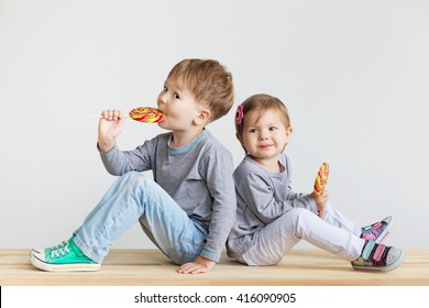 Little children eating lollipops. Happy kids with a big candy. Portrait of a happy little children - boy and girl. Beautiful kids against a white background