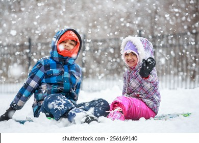 Little Children Enjoying Snowfall and Playing in the Snow