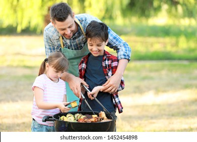 Little children with father cooking tasty food on barbecue grill outdoors