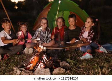 Little children frying marshmallows on bonfire. Summer camp