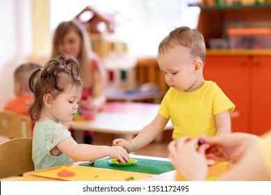 Little children girl and boy molding from play dough in creche