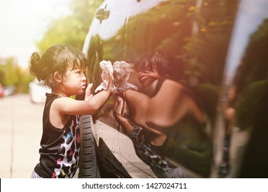 a little children girl washing her father car