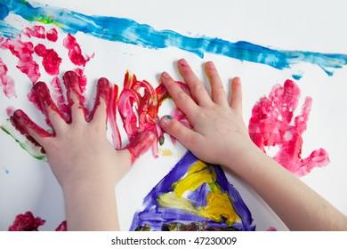 Little Children Hands doing Fingerpainting with vivid colors