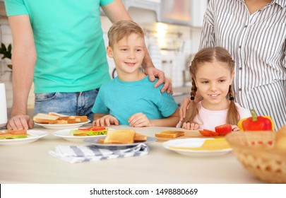 Little children having breakfast with toasts in kitchen