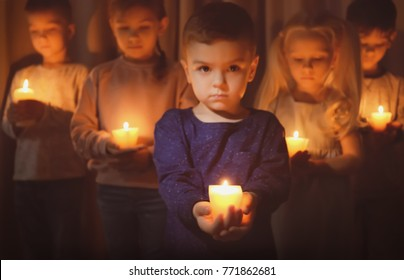 Little children holding burning candles in darkness blur