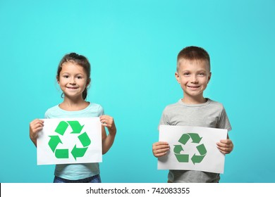 Little children holding paper sheets with recycling symbol on color background