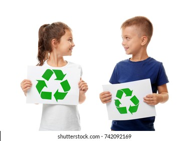 Little children holding paper sheets with recycling symbol on white background