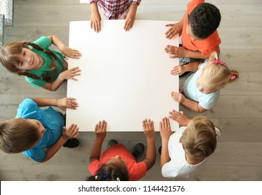 Little children holding sheet of paper in hands together indoors, top view. Unity concept