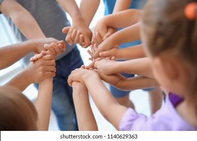 Little children holding their hands together, closeup. Unity concept