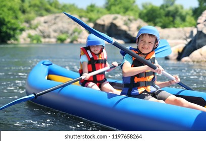 Little children kayaking on river. Summer camp