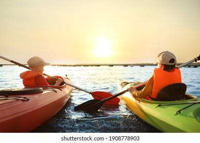 Little children kayaking on river, back view. Summer camp activity