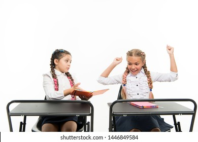 Little children learn reading and writing at school. Reading skills. Opposite impression. Personal attitude determines success. Acquiring knowledge. Small girls with books sit at desks reading lesson.