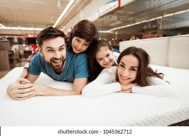 Little children lie on the backs of young happy parents in a mattress store. Big family together check softness of mattress. Orthopedic mattress, for comfortable sleep and healthy posture.