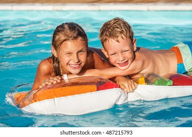 Little children on air mattress playing and having fun in swimming pool. Boy and girl swim in water. Summer vacations concept.