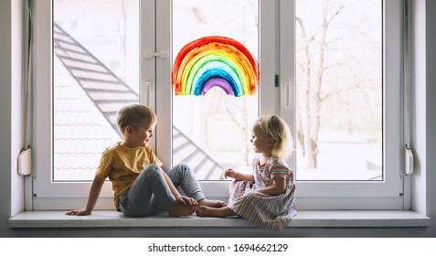 Petits enfants sur fond de peinture en arc-en-ciel sur fenêtre. Photo d'enfants loisirs à la maison. Support visuel positif pendant la quarantaine Coronavirus Covid-19 à la maison. Arrière-plan
