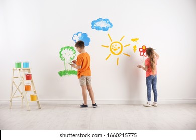 Little children painting on white wall indoors