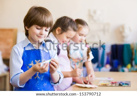 Little children painting and playing at kindergarten